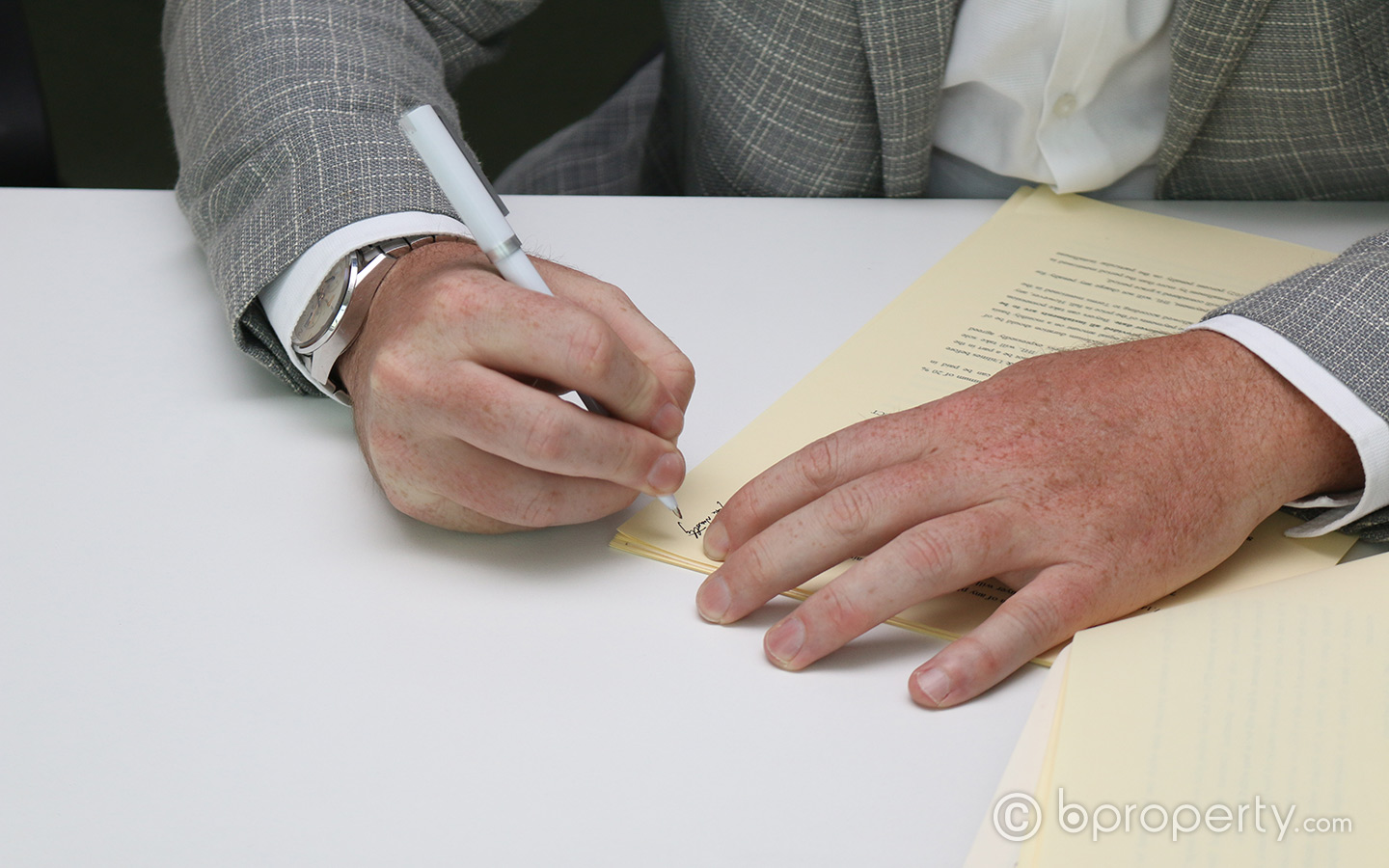 A client signing a property deed