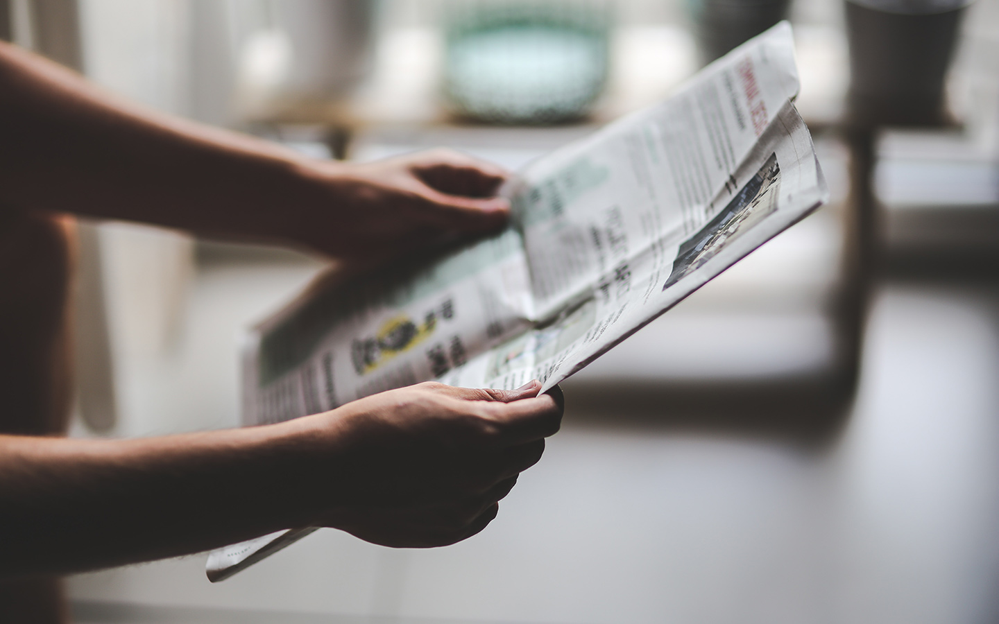 An individual reading newspaper to look for information