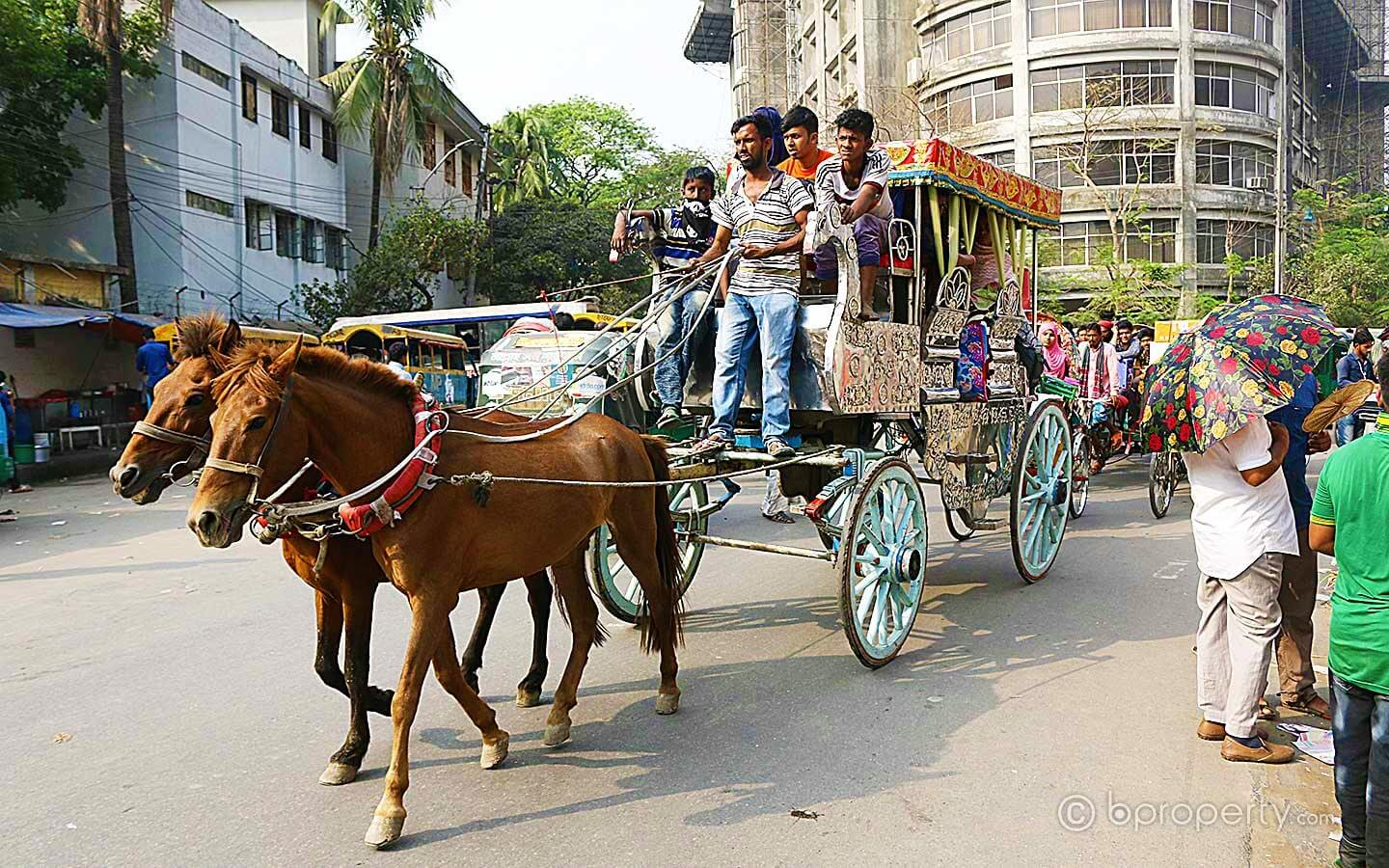 A horse carriage carrying passengers in the streets of old Dhaka