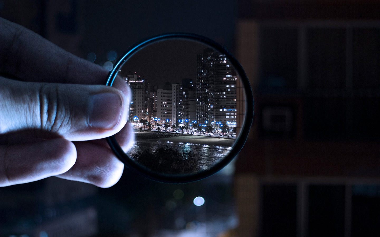 a guy holding magnifying glass to see buildings