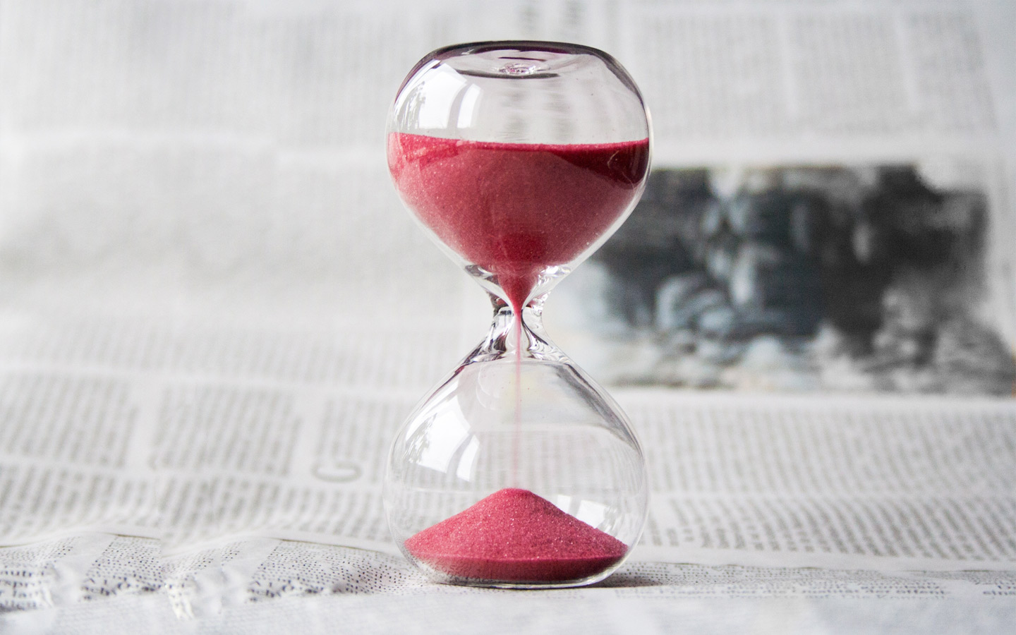 an hourglass placed on a newspaper
