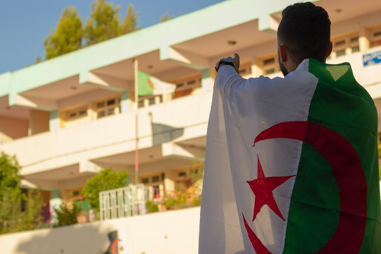 Man with Algerian Flag wrapped around him