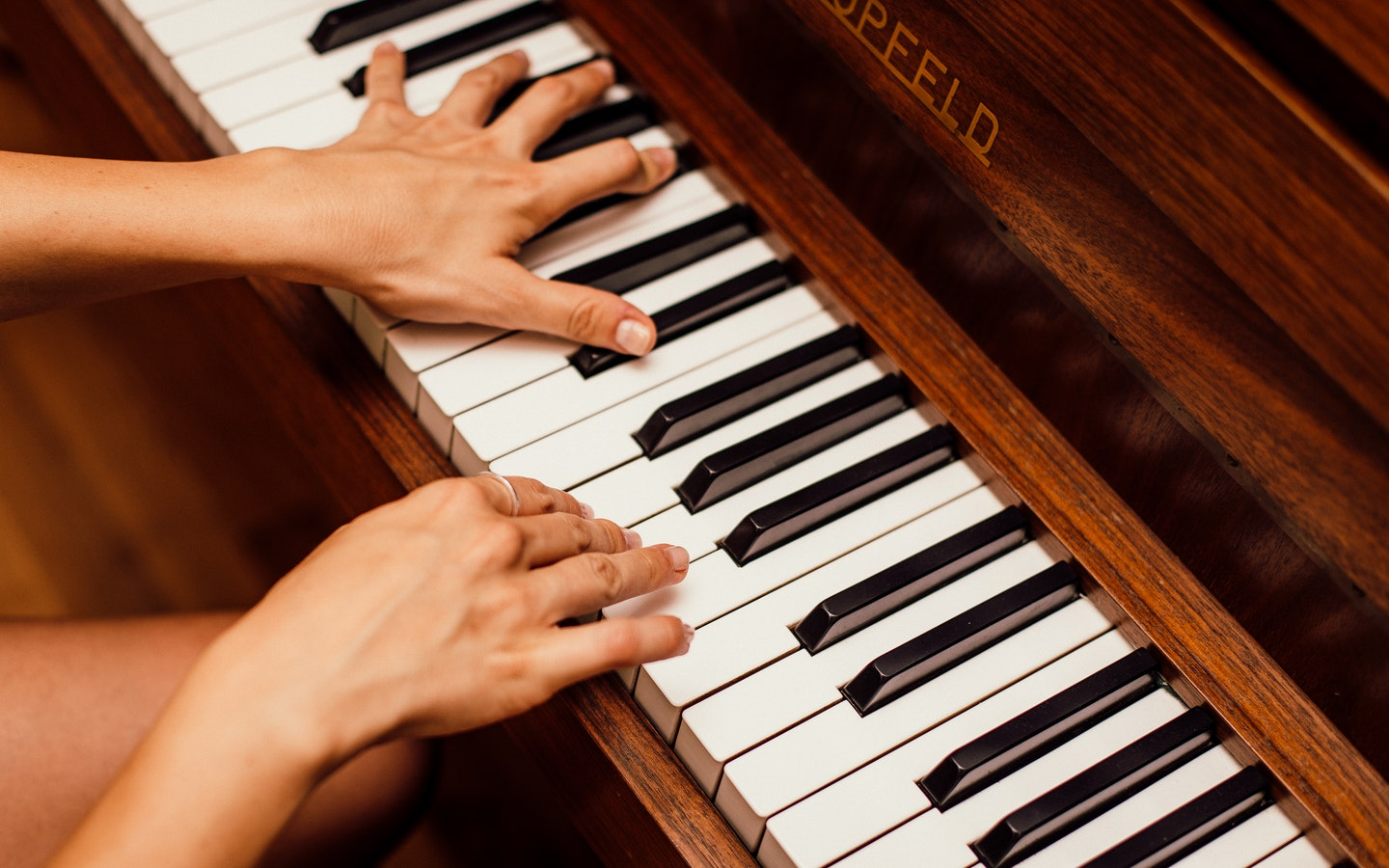 A person playing a piano with two hands