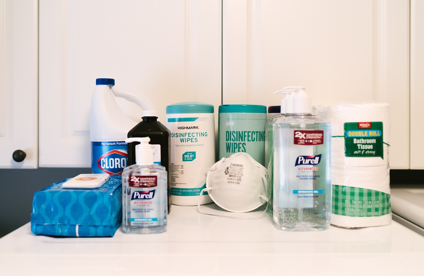 Napkins, disinfectant spray, face mask, and sanitizers on a table