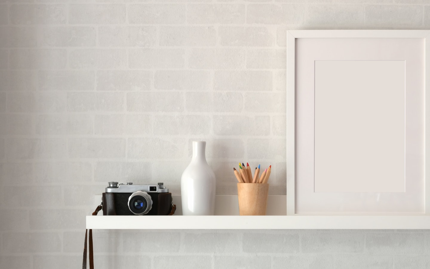 A film camera, pen holder, and a modern painting sitting on a table against a textured wall