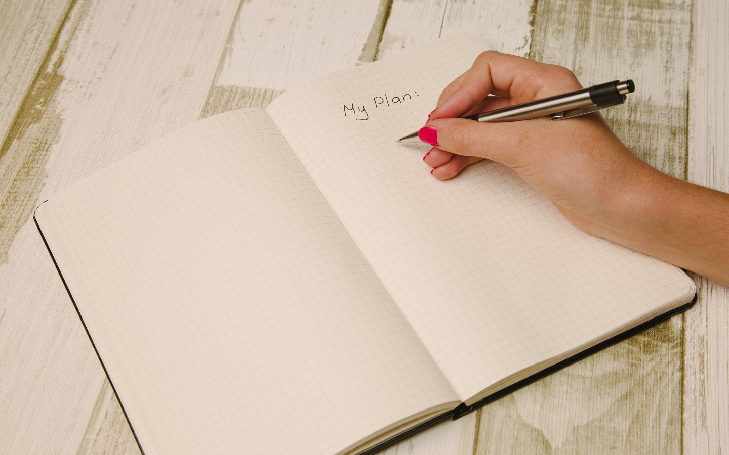 a hand writing on a diary