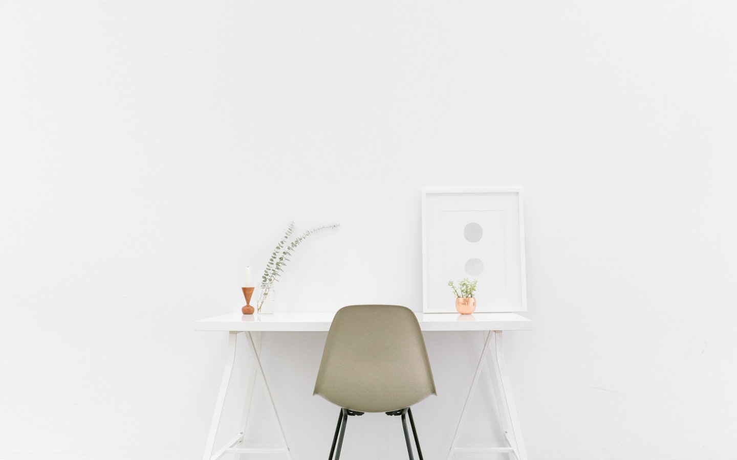 A chair and a table placed in front of a white colored wall