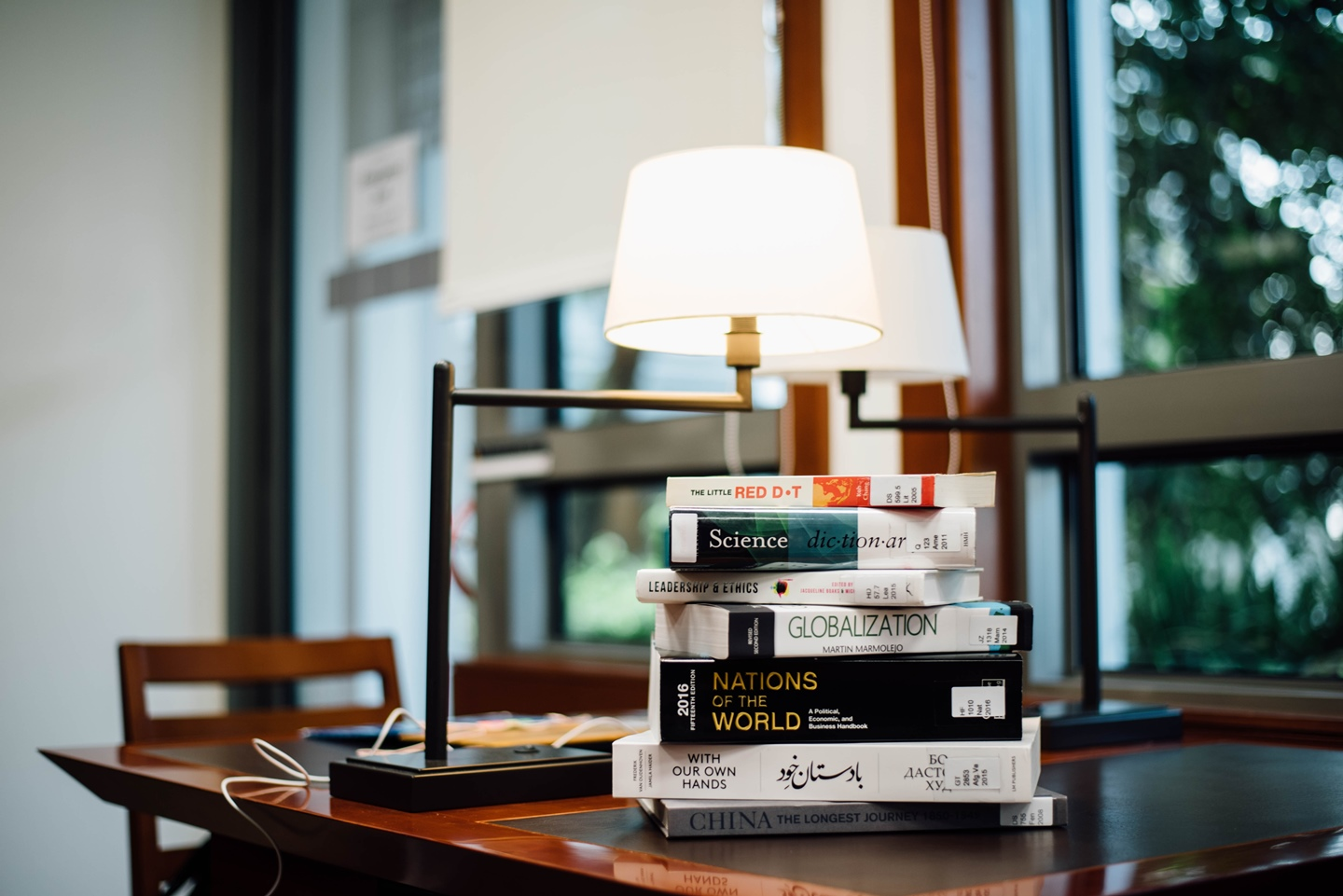 books arranged on the table under a lamp