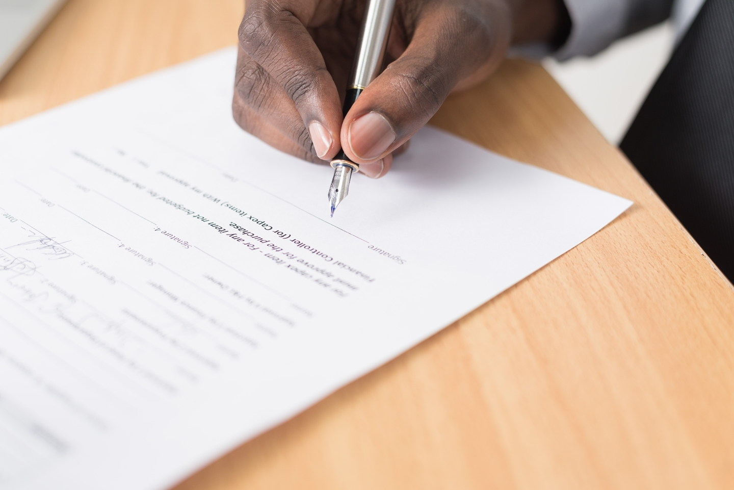 a hand signing a contract paper