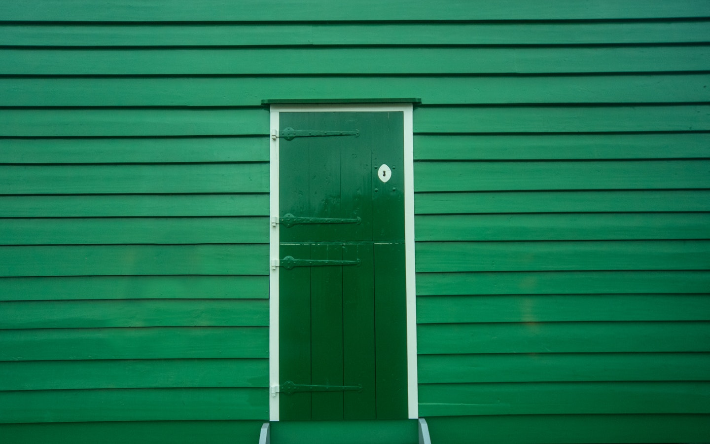 Green door and wooden green house