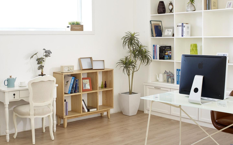 a home office with a desktop setup and bookshelf