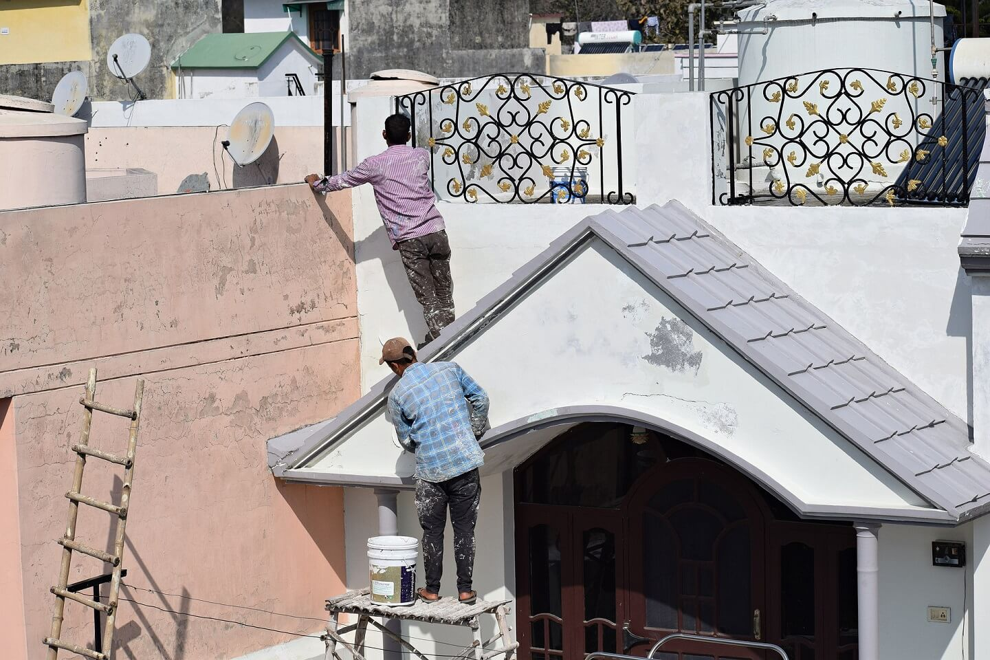 two workers are renovating the exterior of a house