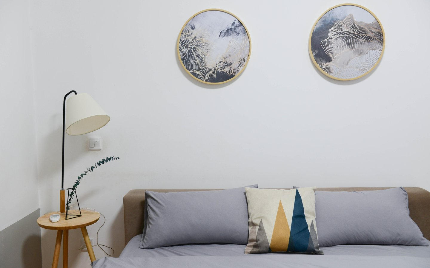 A bed with oval shaped arts on the wall