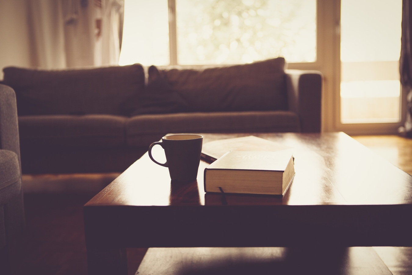 cofee and book on a table with couch on back