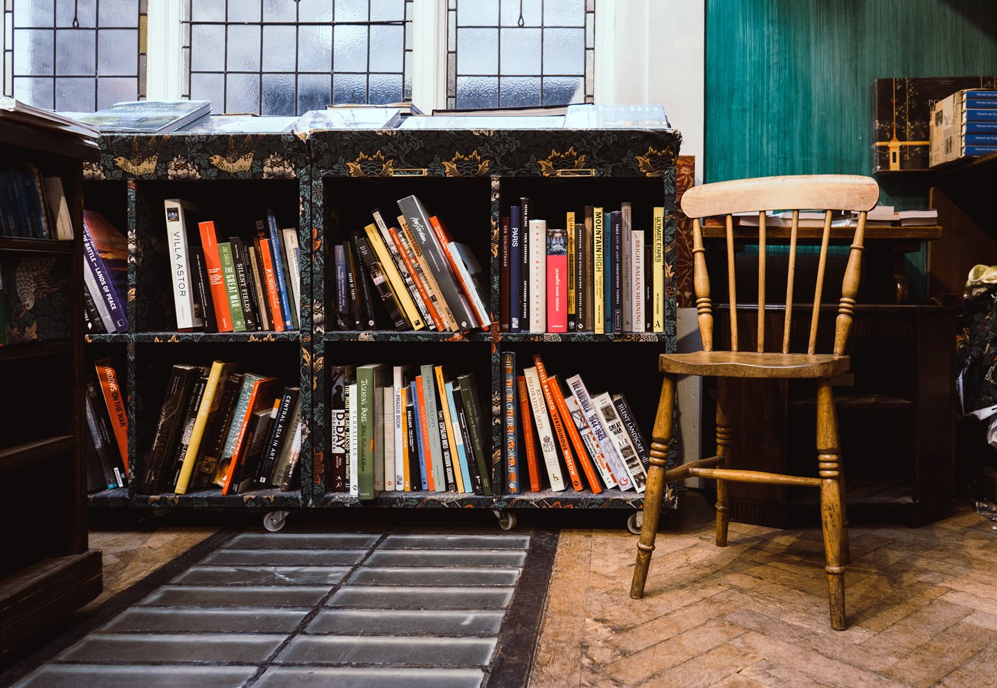 books arranged in shelves with a furnished chair