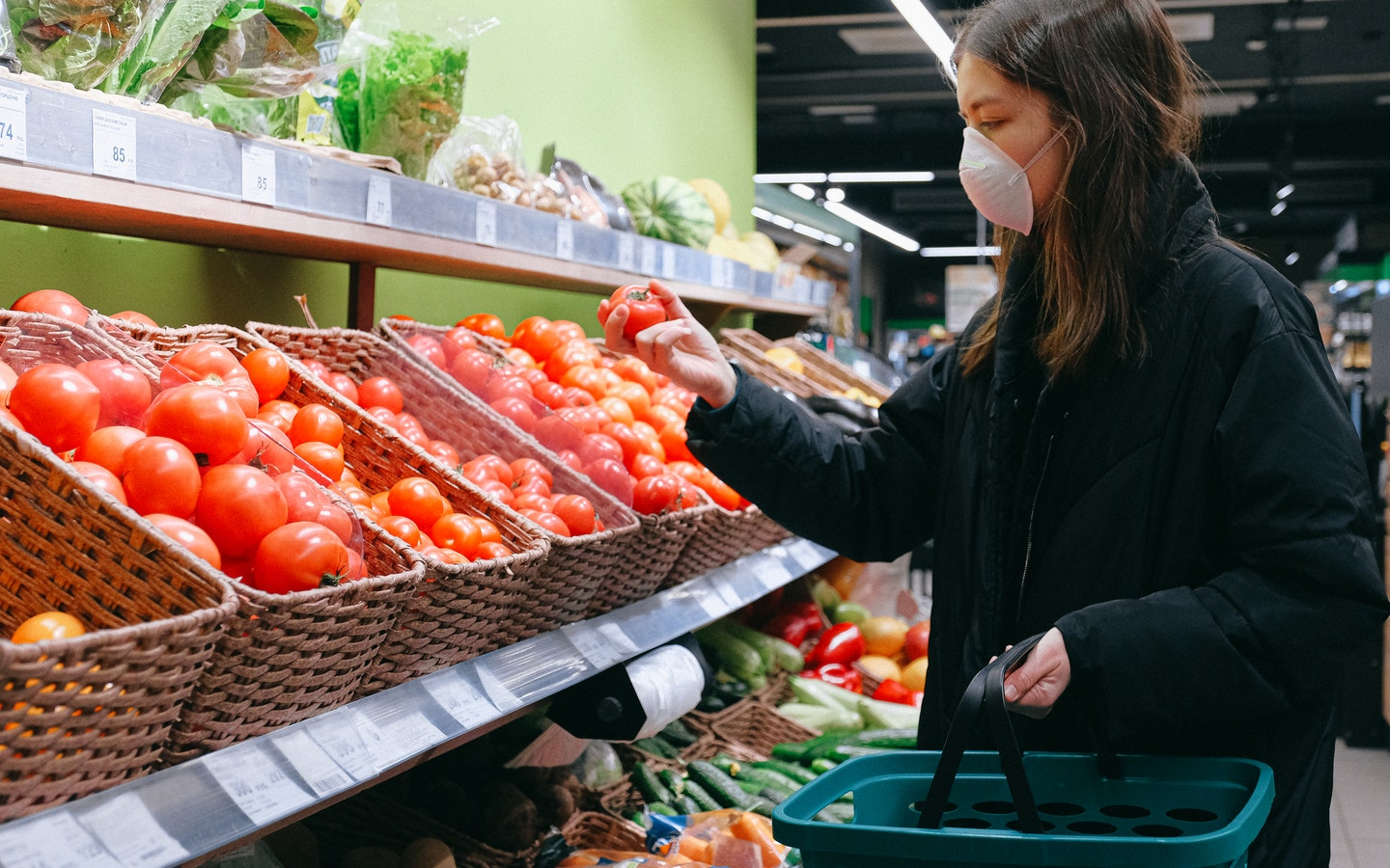 a woman wearing mask is checking a tomato