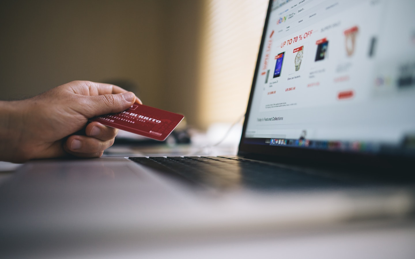 a hand is holding a credit card in front of a computer
